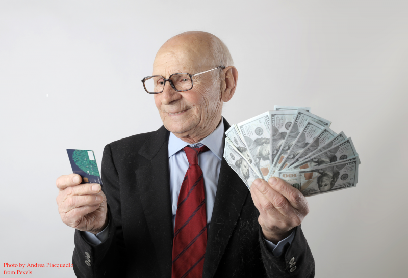Older white man in black suit jacket and red tie holding lots of one hundred dollar bills in one hand and gift card in the other